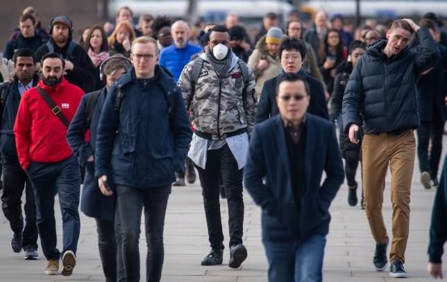 A man wearing a protective face mask as commuters cross London Bridge during morning rush hour in London , as the Government's top scientist warned that up to 10,000 people in the UK are already infected. PA Photo. Picture date: Friday March 13, 2020. See PA story HEALTH Coronavirus. Photo credit should read: Dominic Lipinski/PA Wire