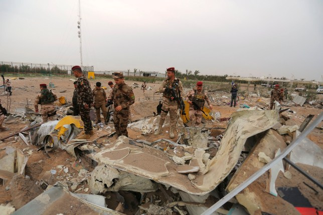 Iraqi army soldiers inspect the destruction at an airport complex under construction in Karbala, Iraq, Friday, March 13, 2020. Iraq's military said five security force members and a civilian were killed early Friday in a barrage of U.S. airstrikes, which were launched hours after a rocket attack killed and wounded American and British servicemen at a base north of Baghdad. (AP Photo/Anmar Khalil)