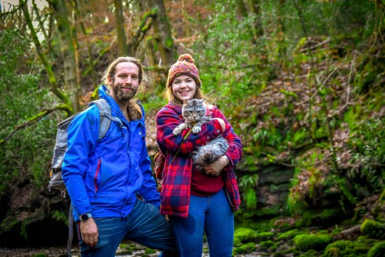PIC BY @the.good.cat/MERCURY PRESS (PICTURED ARLO WITH MARC AND CRISSY) A cat that loves nothing more than going on hour-long dog walks with his canine pals leaves onlookers stunned as he takes on mountainous terrain on a lead. Maine Coon-Tabby cross, Arlo, is just nine months old but has been trekking around the countryside in his hometown of Halifax, West Yorks, since he was a kitten. His owners, Crissy Lister, 29, and Marc Shaw, 31, first discovered his love of the outdoors when they took him to Scafell Pike, in August last year, and have even set up an Instagram page for the fearless feline who joins their dogs, Lexi, a two year old Lurcher and Callie, a three year old Cavalier on their adventures across some of the countys most beautiful scenes. SEE MERCURY COPY.