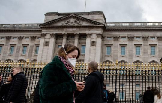 LONDRA, INGHILTERRA - 14 MARZO: Una donna indossa una maschera mentre cammina oltre Buckingham Palace mentre lo scoppio del coronavirus si è intensificato il 14 marzo 2020 a Londra, Inghilterra. Molti londinesi e turisti stanno continuando le loro attività quotidiane mentre le riunioni di massa potrebbero essere bandite nel Regno Unito già dal prossimo fine settimana quando lo scoppio del coronavirus si intensificasse. Molte nazioni in Europa hanno già introdotto severi divieti di viaggio e limiti alla vita quotidiana dei loro cittadini mentre gli Stati Uniti hanno sospeso i viaggi in arrivo dai paesi europei. (Foto di Chris J Ratcliffe / Getty Images)