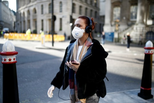 Una donna che indossa una maschera protettiva cammina per la città di Londra mentre il numero di casi di coronavirus in tutto il mondo continua ad aumentare, a Londra, Gran Bretagna, 16 marzo 2020. REUTERS / Henry Nicholls