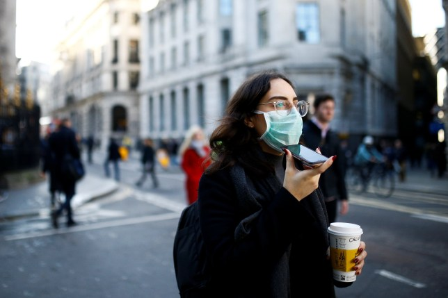 People, some wearing protective face masks, walk through the City of London, as the number of coronavirus cases worldwide continues to grow, in London, Britain, March 16, 2020. REUTERS/Henry Nicholls