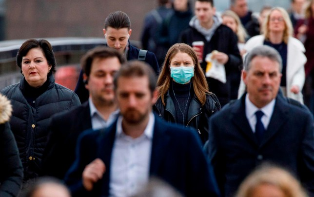 A commuter wears a mask whilst walking across London Bridge into the City of London during the morning rush hour on March 18, 2020 as people take precautions amid the coronavirus outbreak. - The British government will on Wednesday unveil a raft of emergency powers to deal with the coronavirus epidemic, including proposals allowing police to detain potentially infected people to be tested. (Photo by Tolga AKMEN / AFP) (Photo by TOLGA AKMEN/AFP via Getty Images)