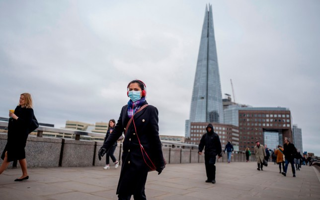 A commuter wears a mask whilst walking across a quiet London Bridge into the City of London
