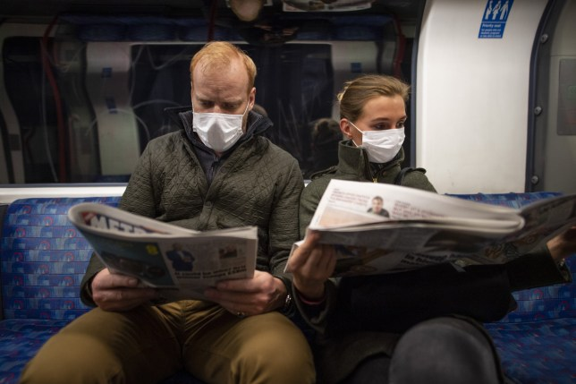 A couple sit on the Central Line Tube wearing protective face masks
