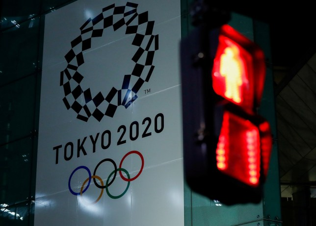 FILE PHOTO : A banner for the upcoming Tokyo 2020 Olympics is seen through a traffic signal in Tokyo, Japan, March 11, 2020. REUTERS/Issei Kato/File Photo