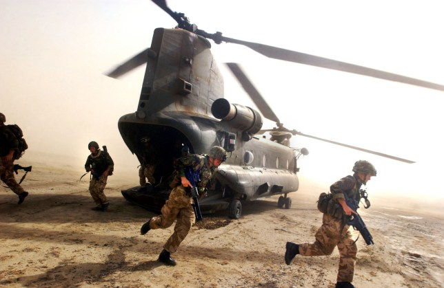 AFGHANISTAN - JULY 8: British Royal Marines of 45 Commando scramble out the back of a Chinook helicopter during an eagle vehicle check point (VCP) operation as part of the ongoing Operation Buzzard July 8, 2002 in southeastern Afghanistan. During VCPs, small groups of marines are dropped quickly by helicopters to search random vehicles on dirt roads and trails near the Pakistan-Afghanistan border to deny al Qaeda and Taliban fighters freedom of movement across the region. (Photo by Scott Nelson/Getty Images)