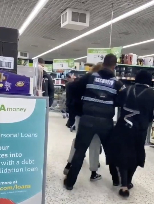 A security guard attempts to remove a woman from the tills in Asda supermarket, before the woman?s mother, right, dramatically pretends to faint in a desperate bid for attention, Roehampton, London Saturday 21st March, 2020. THIS is the bizarre moment a woman pretends to FAINT after she and her daughter get into a physical confrontation with Asda security staff amidst the Coronavirus panic-buying chaos. The incident was filmed this weekend at the Asda Supermarket in Roehampton, Southwest London. The altercation is believed to have erupted between the women and the Asda employees over an argument about being restricted on the number of purchases they could make as supermarkets combat stock-piling. The video has gone viral on Twitter with many social media users comparing the woman to cheating or diving footballers in the Premier League. One online user humorously commented ?She should be signed up by the Premier League!? In the video, the woman?s daughter is seen being manhandled by Asda security staff. The supermarket employees wrestle with her daughter and try to escort her out of the store. ? SEE COPY AND VID ... PIC BY NEWS DOG MEDIA ... 0121 517 0019 ... pictures@newsdogmedia.co.uk