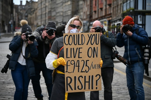A woman wearing a mask, holds a sign which asks Chancellor Rishi Sunak if he could live on the statutory sick pay rate for employees