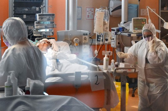 Medical workers in protective gear tend to a patient (Rear L) on March 24, 2020 at the new COVID 3 level intensive care unit for coronavirus COVID-19 cases at the Casal Palocco hospital near Rome, during the country's lockdown aimed at stopping the spread of the COVID-19 (new coronavirus) pandemic. (Photo by Alberto PIZZOLI / AFP) (Photo by ALBERTO PIZZOLI/AFP via Getty Images)