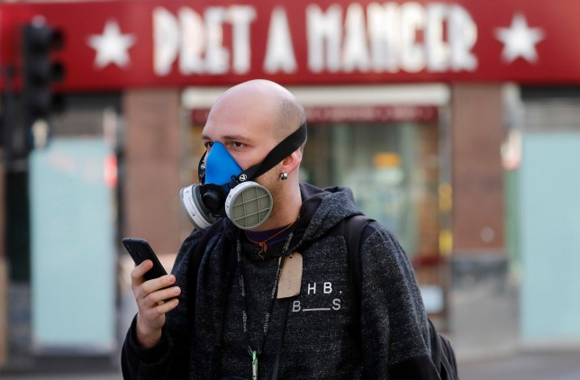 A man wears a mask as he walks through London, Tuesday, March 24, 2020. Britain's Prime Minister Boris Johnson on Monday imposed its most draconian peacetime restrictions due to the spread of the coronavirus on businesses and social gatherings. For most people, the new coronavirus causes mild or moderate symptoms, but for some it can cause more severe illness. (AP Photo/Frank Augstein)