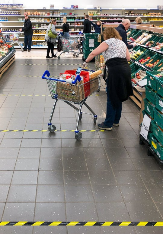 The tape demarcates sections of 2 meters on the ground to implement social distancing measures in a Tesco store