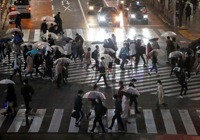 Pedestrians walk past a scramble crossing during the first weekend after Tokyo Governor Yuriko Koike (not in picture) urged the residents to stay indoors in a bid to keep the coronavirus disease (COVID-19) from spreading, at Shibuya shopping and amusement district in Tokyo, Japan March 28, 2020. REUTERS/Issei Kato