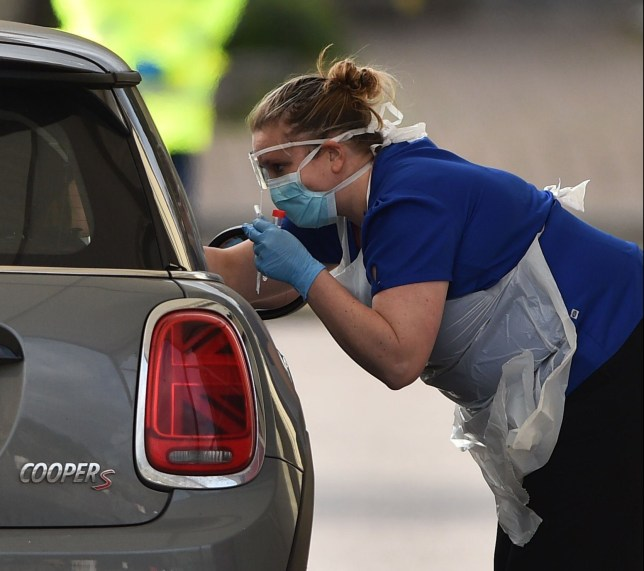 A medical staff member tests an NHS worker for the novel coronavirus COVID-19 at a drive-in facility set up in the carpark of Chessington World of Adventures in Chessington, Greater London on March 28, 2020. - Britain on March 24 said it will open a 4,000-bed field hospital at a London exhibition centre to treat coronavirus cases in the latest measure to tackle the outbreak after the government ordered a nationwide lockdown. (Photo by Glyn KIRK / AFP) (Photo by GLYN KIRK/AFP via Getty Images)