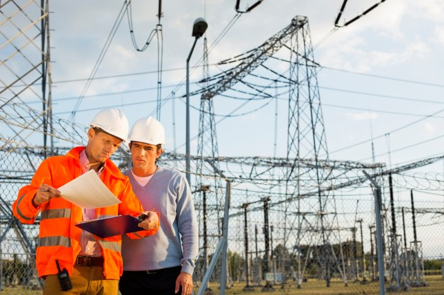 Architects reviewing documents together at electric power plant