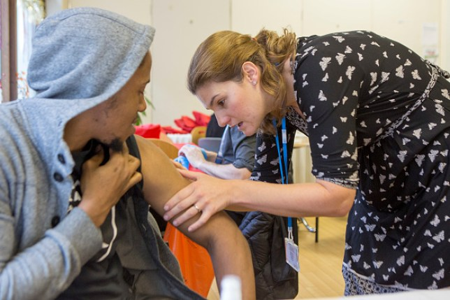 A TB Nurse Specialist checks for a BCG vaccination scar on a young man's arm.
