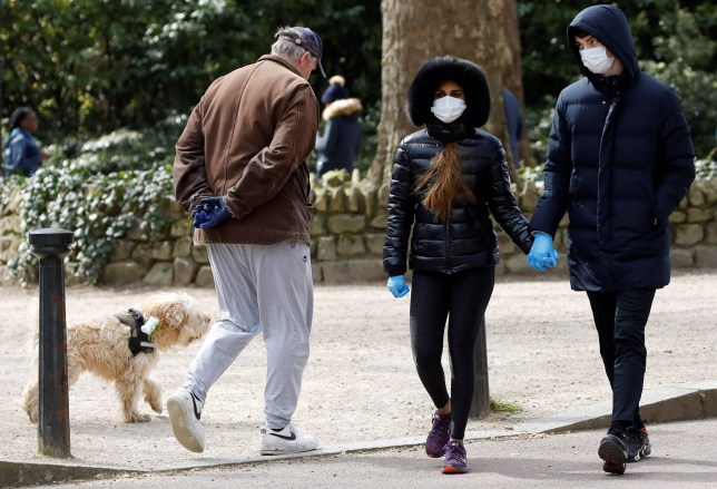 A man walks with a dog as a couple, wearing gloves and face masks a a precautionary measure against Covid-19 walk past to get their daily exercise allowance in Battersea Park in London on March 28, 2020, as life in Britain continues during the nationwide lockdown to combat the novel coronavirus pandemic. - The two men leading Britain's fight against the coronavirus -- Prime Minister Boris Johnson and his Health Secretary Matt Hancock -- both announced Friday they had tested positive for COVID-19, as infection rates accelerated and daily death rate rose sharply. (Photo by Tolga AKMEN / AFP) (Photo by TOLGA AKMEN/AFP via Getty Images)
