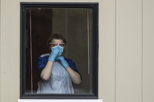 CHESSINGTON, ENGLAND - MARCH 30: A nurse adjusts her face mask before taking swabs at a Covid-19 Drive-Through testing station for NHS staff on March 30, 2020 in Chessington, United Kingdom. The Coronavirus (COVID-19) pandemic has spread to many countries across the world, claiming over 30,000 lives and infecting hundreds of thousands more. (Photo by Dan Kitwood/Getty Images)