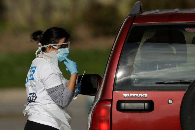 A NHS (National Health Service) worker is tested for Covid-19 at a drive-through testing centre in a car park at Chessington World of Adventures, Greater London, Saturday, April 4, 2020. The new coronavirus causes mild or moderate symptoms for most people, but for some, especially older adults and people with existing health problems, it can cause more severe illness or death. (AP Photo/Matt Dunham)