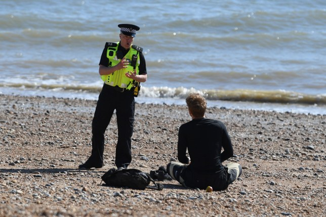 BRIGHTON, ENGLAND - APRIL 04: A police officer moves a member of the public off Brighton beach on April 04, 2020 in Brighton, England. The Coronavirus (COVID-19) pandemic has spread to many countries across the world, claiming over 50,000 lives and infecting over 1 million people. (Photo by Mike Hewitt/Getty Images)