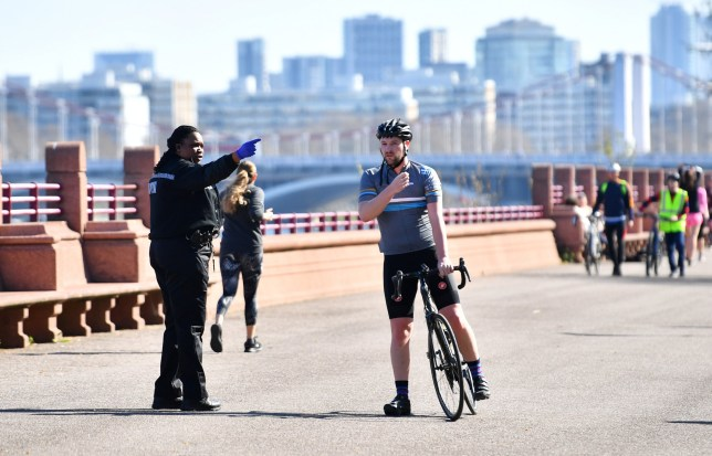 A police officer talks to a cyclist in Battersea Park, as the spread of the coronavirus disease (COVID-19) continues, London, Britain, April 5, 2020. REUTERS/Dylan Martinez