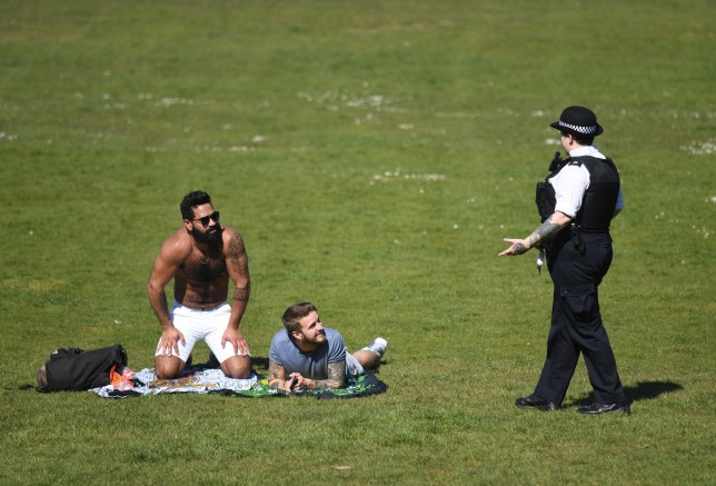 epa08344113 Police speaks to people sunbathing in Greenwich Park on a sunny day in London, Britain, 05 April 2020. Britain's Health Secretary Matt Hancock warned exercise outside the home could be banned if people ignore coronavirus social distancing rules. Britain's Prime Minister Boris Johnson has implemented social distancing measures banning social gatherings and groups of more than two people. People must stand more than two metres apart. EPA/NEIL HALL