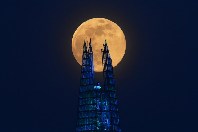 The Pink Supermoon rises over the Shard skyscraper in London in an astronomical event that occurs when the moon is closest to the Earth in its orbit, making it appear much larger and brighter than usual, in London, Britain, April 7, 2020. REUTERS/Dylan Martinez