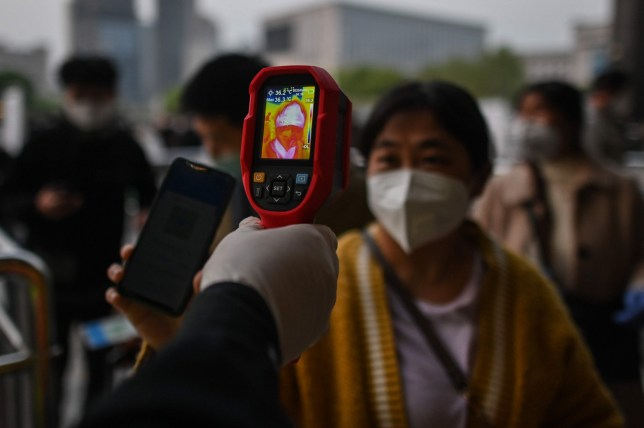 A worker controls the temperature of a woman wearing a face mask as she arrives at Hankou Railway Station in Wuhan, to board one of the first trains leaving the city in China's central Hubei province early on April 8, 2020. - Chinese authorities lifted a more than two-month ban on outbound travel from the city where the global pandemic first emerged. (Photo by Hector RETAMAL / AFP) (Photo by HECTOR RETAMAL/AFP via Getty Images)