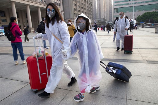 Passengers wearing face masks and raincoats to protect themselves from the spread of new coronaviruses walk outside Hankou station after rail services resume in Wuhan, central China's Hubei Province on Wednesday 8 April 2020. After 11 weeks of lockout, the first train left on Wednesday morning from a reopened Wuhan, the source of the coronavirus pandemic, as residents were again allowed to travel in and out of the city sprawling central China. (Photo AP / Ng Han Guan)