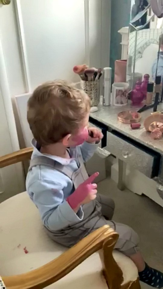 Video grab of the hilarious moment two-year-old Oscar got into his mum's makeup and covered his face in pink lipstick.