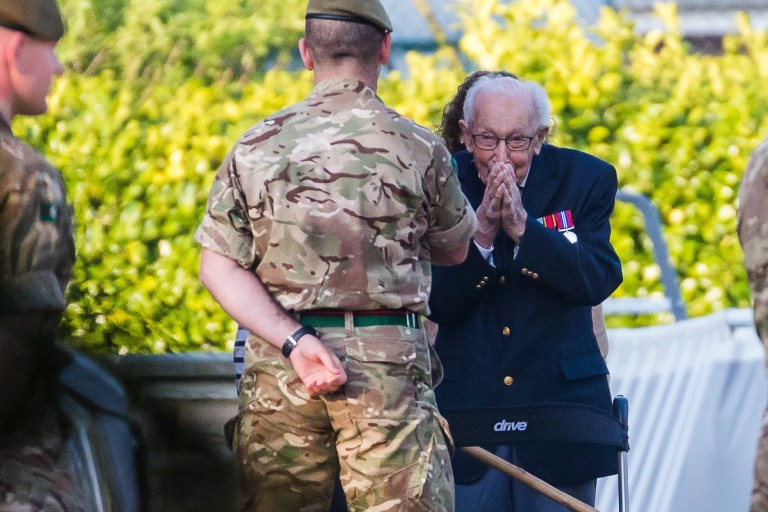 epa08365722 99-year-old British veteran Captain Tom Moore (R) reacts as he completes the 100th length of his back garden in Marston Moretaine, Bedfordshire, Britain, 16 April, 2020. Captain Tom Moore has raised over ??12 million for Britain???s National Health Service (NHS) and has received donations to his fundraising challenge from around the world. EPA/VICKIE FLORES