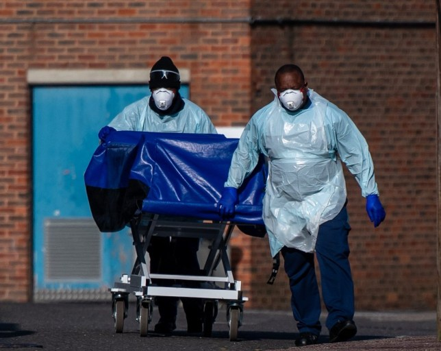 LONDON, ENGLAND - APRIL 16: Hospital workers wheel a concealment trolley, typically used for transporting bodies, to the mortuary at Lewisham Hospital on April 16, 2020 in London, UK. The Lewisham and Greenwich NHS Trust, which runs Lewisham Hospital and Queen Elizabeth Hospital in Greenwich, reported 14 deaths from Covid-19 occurring between March 27 and April 12. The hospital recently installed refrigerated containers in its car park. The Coronavirus (COVID-19) pandemic has spread to many countries across the world, claiming over 130,000 lives and infecting over 2 million people. (Photo by Chris J Ratcliffe/Getty Images)