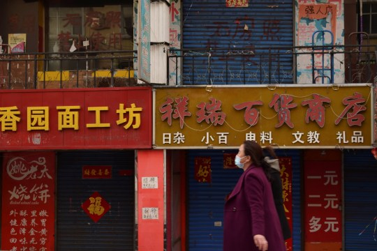 Des femmes portant des masques faciaux passent devant des magasins fermés à la suite d'une épidémie de coronavirus (COVID-19), à Suifenhe, une ville frontalière de la Russie dans la province chinoise du Heilongjiang, le 16 avril 2020.