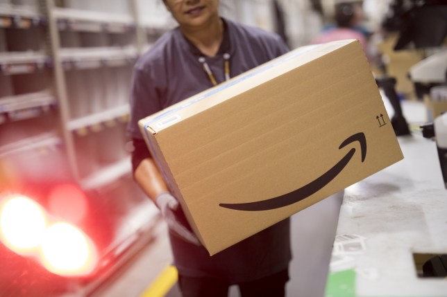 An employee carries a box at the Amazon.com Inc. fulfilment centre in Tilbury, U.K. on Friday, July 12, 2019. By offering 12 extra hours of deals during this year's Prime Day, Amazon will pull in nearly 50% more in sales, according to an estimate from Coresight Research. Photographer: Jason Alden/Bloomberg via Getty Images