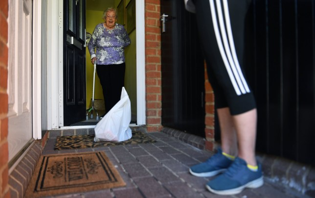 epa08383894 A volunteer from Bucks Angels C-19 Community Group delivers urgent supplies to an elderly lady in High Wycombe, Buckinghamshire, Britain, 25 April, 2020. Bucks Angels have been set up by volunteers as a response to growing concern for the elderly and vulnerable people who are self isolating during the Coronavirus outbreak. Britons are now in their fifth week of lockdown due to the Coronavirus pandemic. Countries around the world are taking increased measures to stem the widespread of the SARS-CoV-2 coronavirus which causes the Covid-19 disease. EPA/ANDY RAIN
