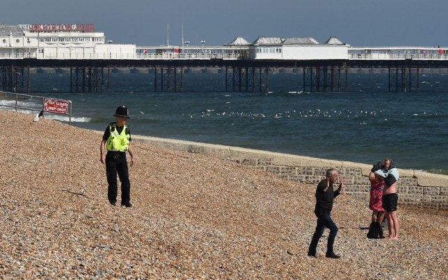 A man walks away after speaking with a police officer on a relatively empty beach in front of Brighton Pier in Brighton, on the south coast of England, on April 25, 2020, during the national lockdown due to the novel coronavirus COVID-19 pandemic. - Britain's health ministry on Saturday said 813 more people had died after testing positive for COVID-19 in hospital, taking the death toll to 20,319. The figure is an increase on the 684 reported the previous day and comes after the government claimed the virus had hit its peak. (Photo by Glyn KIRK / AFP) (Photo by GLYN KIRK/AFP via Getty Images)