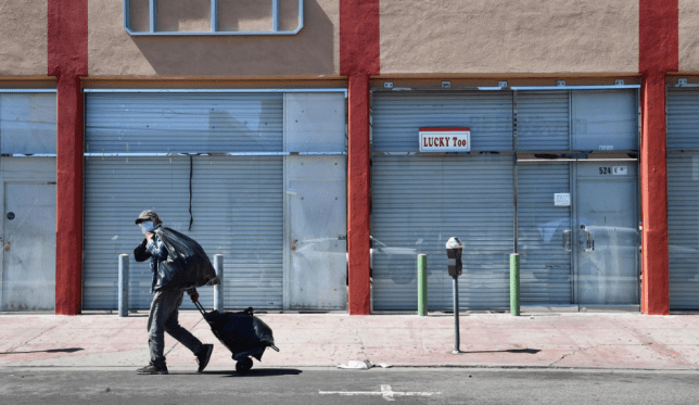 Photo of man walking past shuttered store