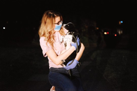 A woman with a face mask holding a dog