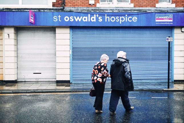 Pedestrians pass a charity shop.