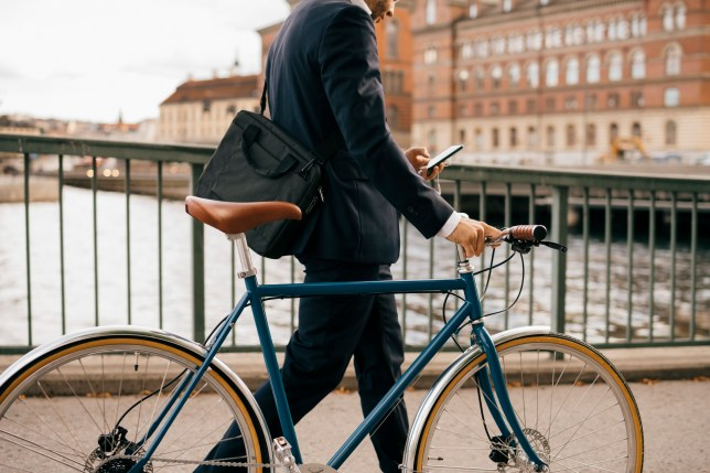 Midsection of businessman using smart phone while walking with bicycle on bridge in city.