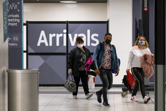 Travelers, wearing a protective face masks, pass through the arrivals area after landing at London Luton Airport.