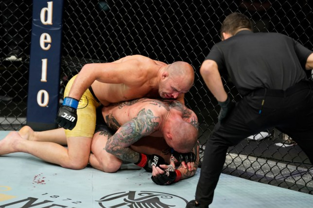 Anthony Smith is punched by Glover Teixeira in their UFC fight