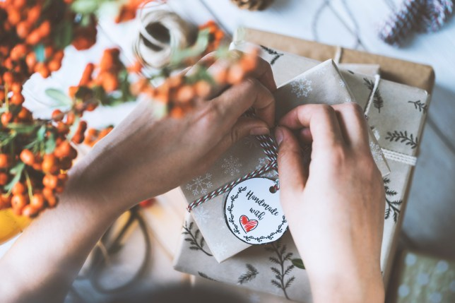 Woman hands gift wrapping Christmas presents, handmade with love.