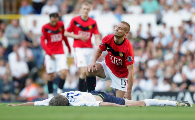 Peter Crouch lies stretched on the pitch after a tackle from Nemanja Vidic