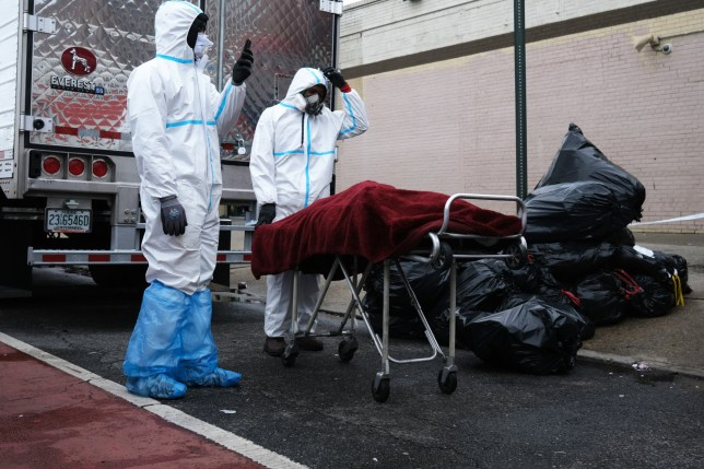 NEW YORK, NY - APRIL 30: A body is moved on the street outside the Andrew Cleckley Funeral Home on April 30, 2020 in the Brooklyn borough of New York City. Dozens of bodies have been discovered in unrefrigerated overflow trucks outside the business following a complaint of a foul odor. The Department of Environmental Protection has issued two summonses to the owner of the funeral home. From grave diggers, to crematoriums and morgues, the funeral industry in New York City has been overwhelmed as COVID-19 continues to kill hundreds of residents daily. (Photo by Spencer Platt/Getty Images)