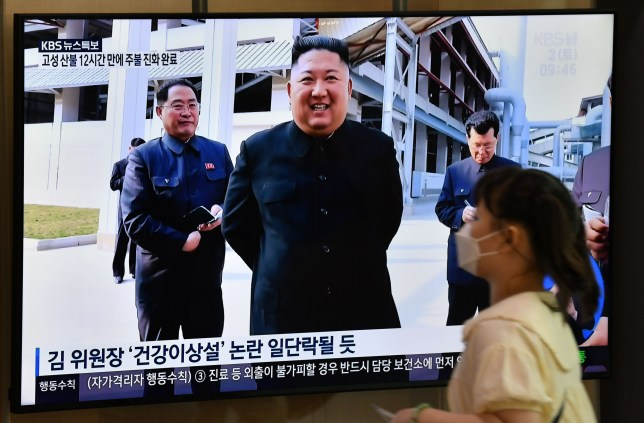 A woman walks past a television news screen showing a picture of North Korean leader Kim Jong Un attending a ceremony to mark the completion of Sunchon phosphatic fertiliser factory, at a railway station in Seoul on May 2, 2020. - North Korea's Kim Jong Un has made his first public appearance in nearly three weeks, state media reported on May 2, following intense speculation that the leader of the nuclear-armed nation was seriously ill or possibly dead. (Photo by Jung Yeon-je / AFP) (Photo by JUNG YEON-JE/AFP via Getty Images)
