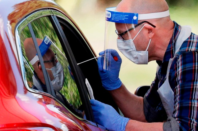 A medical worker takes a swab to test for coronavirus at the drive-through test centre in the Chessington World of Adventures Resort