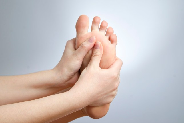 Pain in the foot. Massage of female feet. Pedicures. Studio shot on a gray background.