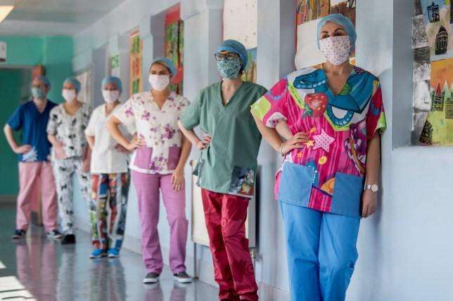 Nurses at Glasgow Royal Infirmary get their hands on a set of wacky scrubs made by 20 volunteers using materials donated at Hyndland Secondary School. See SWNS story SWSCscrubs. Nurses have been boosting morale at a busy hospital by wearing 'funky scrubs' made from colourful bedding. More than 100 sets of scrubs in jazzy colours and patterns have been made for medics at the Glasgow Royal Infirmary. The zany scrubs are made by a group of around 20 volunteers who created them from donated materials at Hyndland Secondary School in Glasgow. Kay Muir, 56, was inspired to set up the Scrub Hub as part of Med Supply Drive Scotland?s initiative to get PPE for frontline hospital staff, which her niece, Gillian Higgins, a surgical trainee at GRI, co-ordinates.