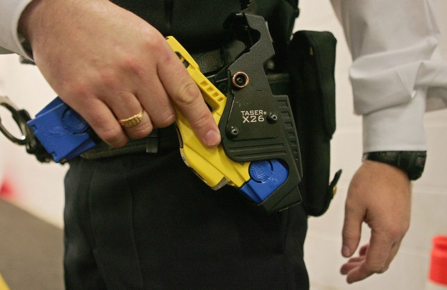 (FILES) A British police officer holsters a taser gun during a training session at the Metropolitan Police Specialist Training Centre, in Gravesend, Kent, in south-east England, 05 December 2007. Taser guns are to be issued to London's Metropolitan Police from Monday 10 December 2007. AFP PHOTO/CARL DE SOUZA/FILES (Photo credit should read CARL DE SOUZA/AFP via Getty Images)